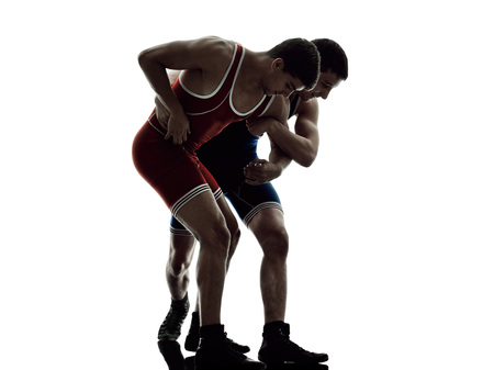 greco roman: two caucasian wrestlers wrestling men on isolated silhouette white background Stock Photo