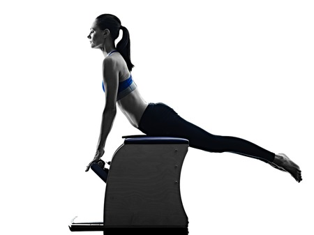 pilates woman: one caucasian woman exercising pilates chair exercises fitness in silhouette isolated on white backgound