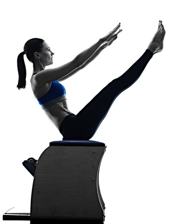 exercise machine: one caucasian woman exercising pilates chair exercises fitness in silhouette isolated on white backgound