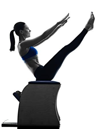ejercicio: una mujer cauc�sica ejercicio silla pilates ejercicios de fitness en la silueta aislado en el backgound blanco Foto de archivo