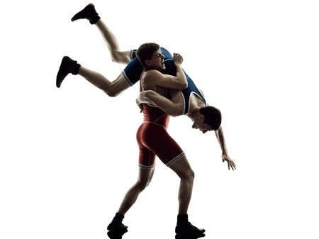 two caucasian wrestlers wrestling men on isolated silhouette white background Фото со стока
