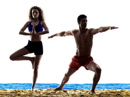exercices: one caucasian couple man and woman yoga exercices on the beach silhouette isolated on white background