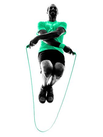 iluminado a contraluz: un hombre saltar la cuerda que ejercita en la silueta aislado en el fondo blanco