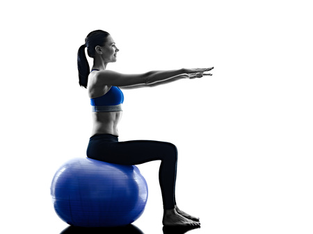 ein kaukasisch Frau Pilates Ball Ausübung Fitness-Übungen in der Silhouette auf weißen Hintergrund isoliert Standard-Bild