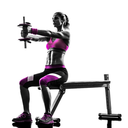 body building: one caucasian woman exercising   weights body building fitness in studio silhouette isolated on white background Stock Photo