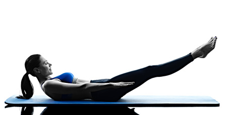 pilates woman: one caucasian woman exercising pilates exercises fitness in silhouette isolated on white backgound