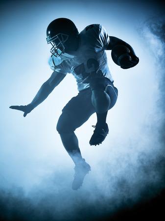 jugadores de futbol: retrato jugador de fútbol americano en la sombra de la silueta en el fondo blanco Foto de archivo