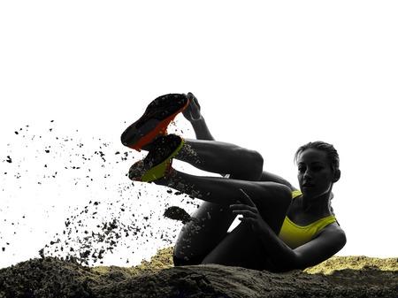 saltando: una mujer praticing silueta de salto de longitud en el estudio de la silueta aislado en el fondo blanco Foto de archivo