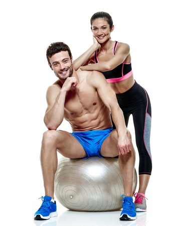 swiss ball: one caucasian couple man and woman exercising fitness exercises isolated on white background Stock Photo