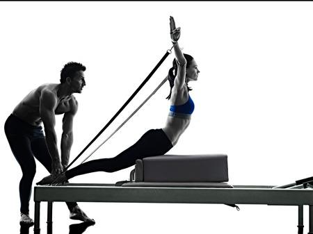een blanke paar uitoefenen pilates reformator oefeningen fitness in silhouet geïsoleerd op witte achtergrondkleur