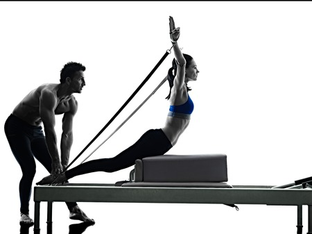 one caucasian couple exercising pilates reformer exercises fitness in silhouette isolated on white backgound Standard-Bild