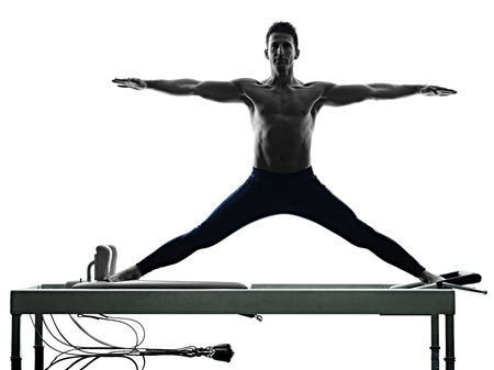 one caucasian man exercising pilates reformer exercises fitness in silhouette isolated on white backgound Фото со стока