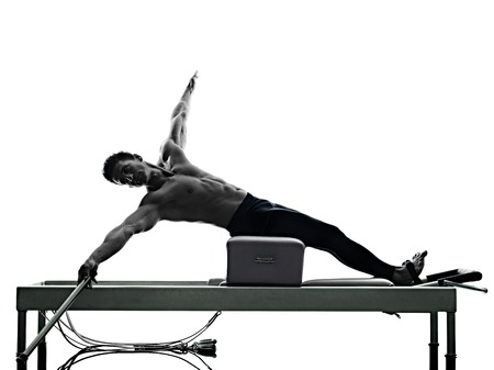 one caucasian man exercising pilates reformer exercises fitness in silhouette isolated on white backgound Standard-Bild