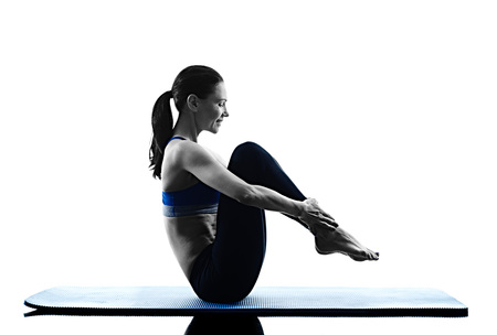 shadow woman: one caucasian woman exercising pilates exercises fitness in silhouette isolated on white backgound