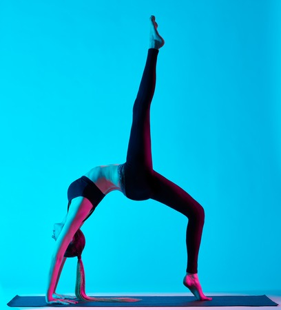 exercices: one caucasian woman exercising yoga exercices  in silhouette studio isolated on blue background