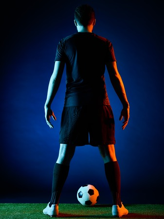 back view: one caucasian Soccer player Man isolated on black backgound