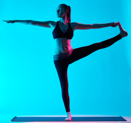 exercices: one caucasian woman exercising Hasta Padangusthasana yoga exercices  in silhouette studio isolated on blue background Stock Photo