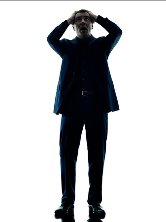 displeased businessman: one caucasian business man standing despair silhouette isolated on white background Stock Photo