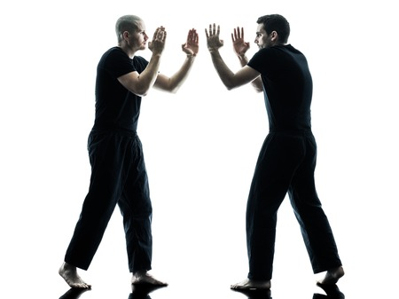 combative: two caucasian men krav maga fighters fighting isolated silhouette on white background
