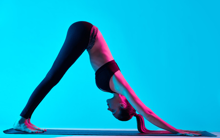 exercices: one caucasian woman exercising yoga Adho Mukha Svanasana exercices  in silhouette studio isolated on blue background