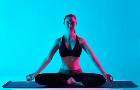 exercices: one caucasian woman exercising Padmasana Lotus position yoga exercices  in silhouette studio isolated on blue background Stock Photo