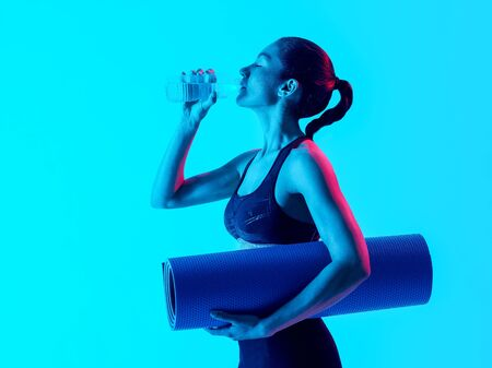 exercices: one mixed races woman exercsing fitness exercices drinking water  isolated on blue blackground Stock Photo