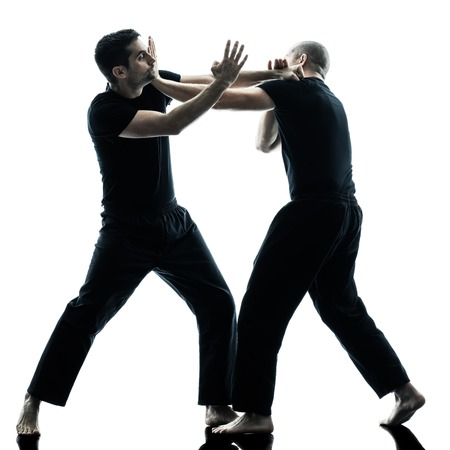 two caucasian men krav maga fighters fighting isolated silhouette on white background