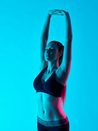exercices: one caucasian woman exercising yoga exercices Tadasana mountain pose in silhouette studio isolated on blue background