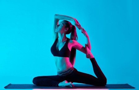 exercices: one caucasian woman exercising  Rajakapotasana  King pigeon yoga exercices  in silhouette studio isolated on blue background