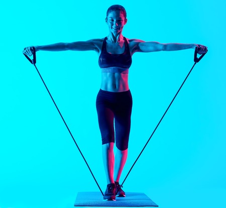 exercices: one mixed races woman exercsing fitness exercices isolated on blue blackground
