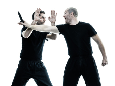 two caucasian men krav maga fighters fighting isolated silhouette on white background Imagens - 57094633