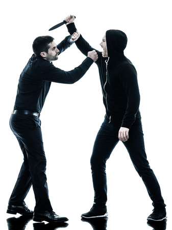 violence in sports: two caucasian men krav maga fighters fighting isolated silhouette on white background