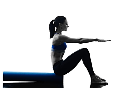iluminado a contraluz: una mujer caucásica ejercicio rodillo de pilates ejercicios de fitness en la silueta aislado en el backgound blanco