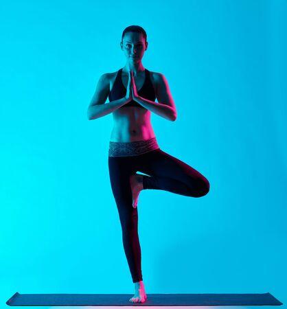 vriksasana: one caucasian woman exercising tree pose Vriksasana yoga exercices  in silhouette studio isolated on blue background