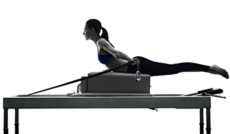 one caucasian woman exercising pilates reformer exercises fitness in silhouette isolated on white backgound 写真素材