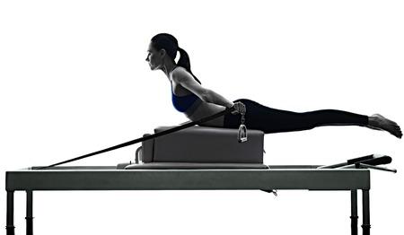 een blanke vrouw te oefenen pilates reformator oefeningen fitness in silhouet geïsoleerd op witte achtergrondkleur