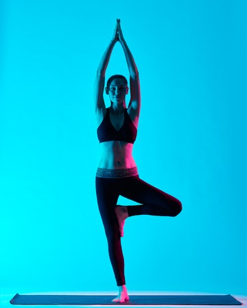 vriksasana: one caucasian woman exercising tree pose Vriksasana yoga exercices  in silhouette studio isolated on blue background