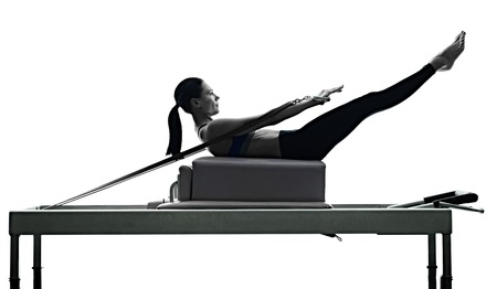 one caucasian woman exercising pilates reformer exercises fitness in silhouette isolated on white backgound Фото со стока