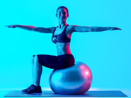 exercices: one mixed races woman exercsing fitness pilates exercices isolated on blue blackground Stock Photo
