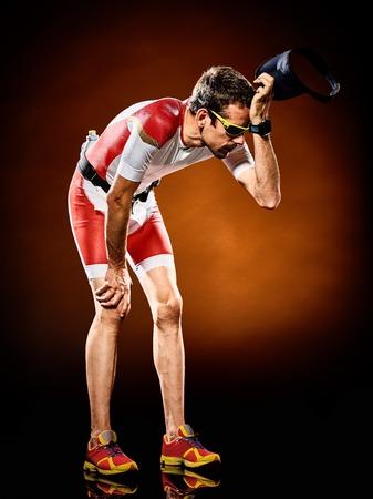 exhausted: one caucasian  man runner running  triathlon ironman isolated