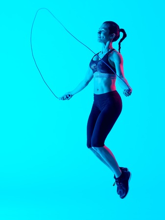 exercices: one mixed races woman exercsing jumping rope fitness exercices isolated on blue blackground