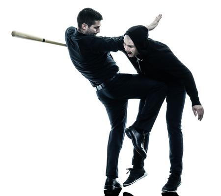 iluminado a contraluz: dos caucásicos combatientes maga del krav hombres que luchan silueta aislados sobre fondo blanco