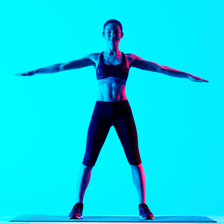 exercices: one mixed races woman exercsing stretching fitness exercices isolated on blue blackground
