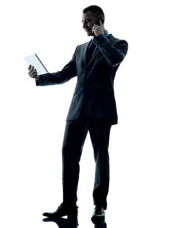 computer isolated: one caucasian business man standing using digital tablet and telephone silhouette isolated on white background
