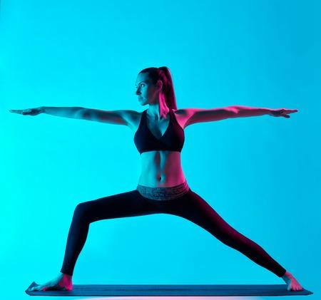 one caucasian woman exercising Virabhadrasana warrior position  yoga exercices  in silhouette studio isolated on blue background Stock Photo