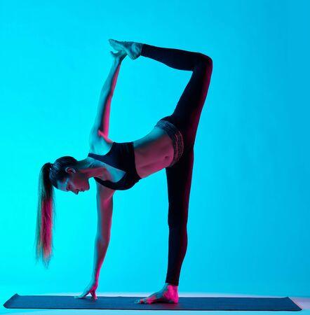 chandrasana: one caucasian woman exercising Ardha Chandrasana  half moon pose yoga exercices  in silhouette studio isolated on blue background