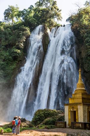 PYIN OO LWIN, MYANMAR - NOVEMBER 29, 2016 :  two young woman praying in front of Dat Taw Gyaint Waterfall Anisakan Pyin Oo Lwin Mandalay state Myanmar