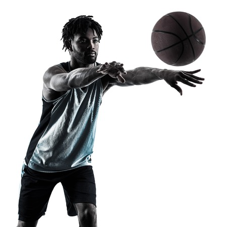 shadow silhouette: one afro-american african basketball player man isolated in silhouette shadow on white background Stock Photo