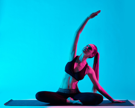 one caucasian woman exercising yoga exercices  in silhouette studio isolated on blue background photo