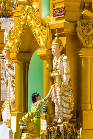 YANGON, MYANMAR - DECEMBER 16, 2016 : woman praying at Shwedagon Pagoda Yangon (Rangoon) in Myanmar (Burma)